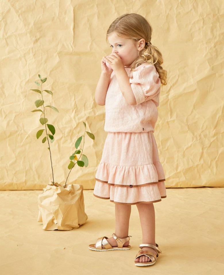 画像:袖のボリューム感が女の子らしいパフスリーブブラウスと、膝を覆う丈感のラブリーな二段スカートのセットコーデ
